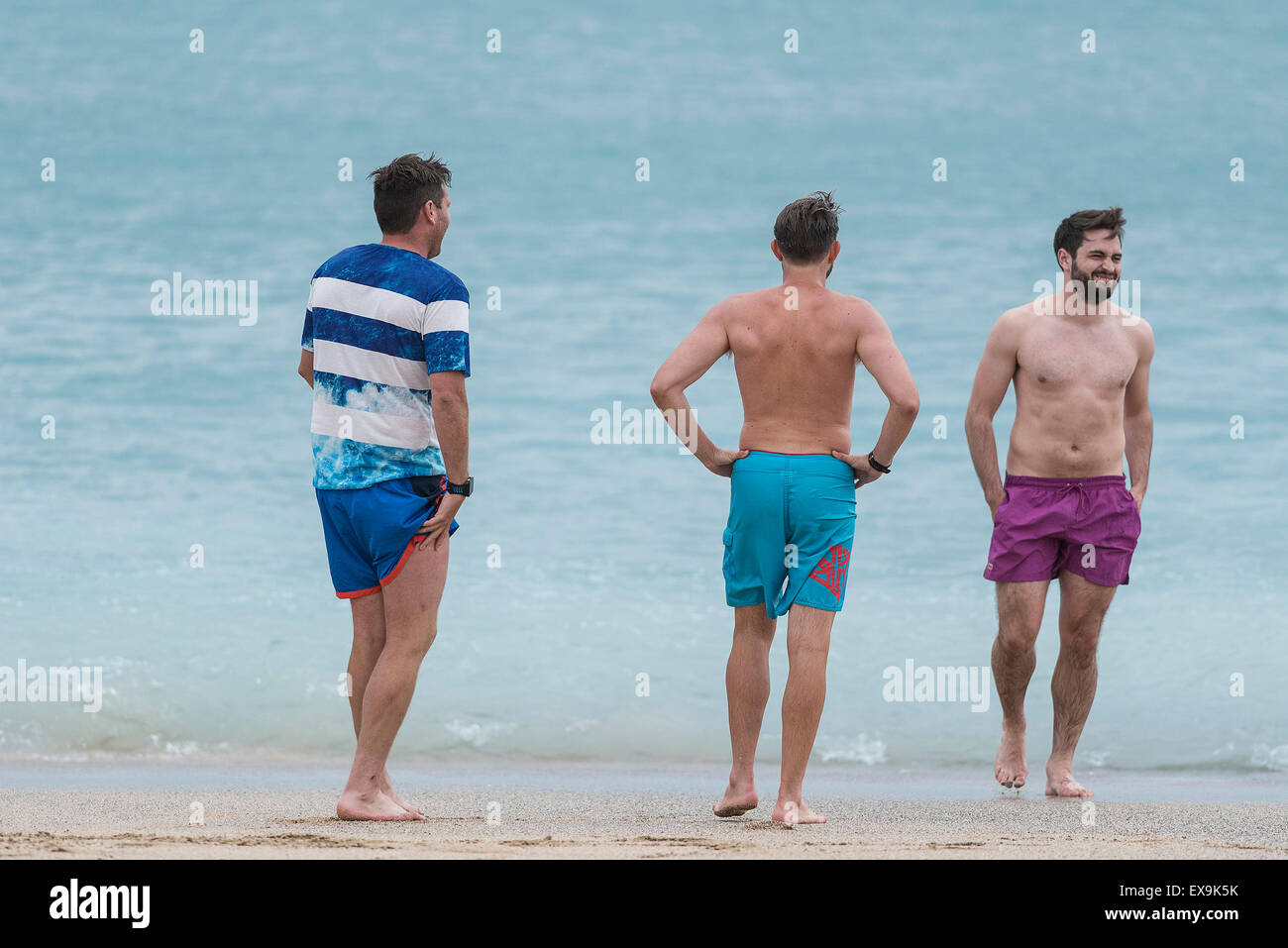 Three holidaymakers on Fistral beach in Newquay, Cornwall. - Stock Image