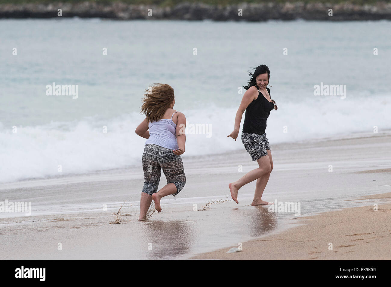 Holidaymakers playingnin the sea at Fistral beach in Newquay, Cornwall. - Stock Image