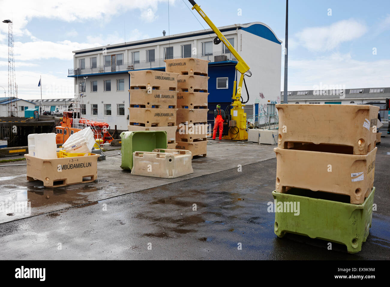 unloading fish boxes from fishing boats in reykjavik harbour iceland - Stock Image