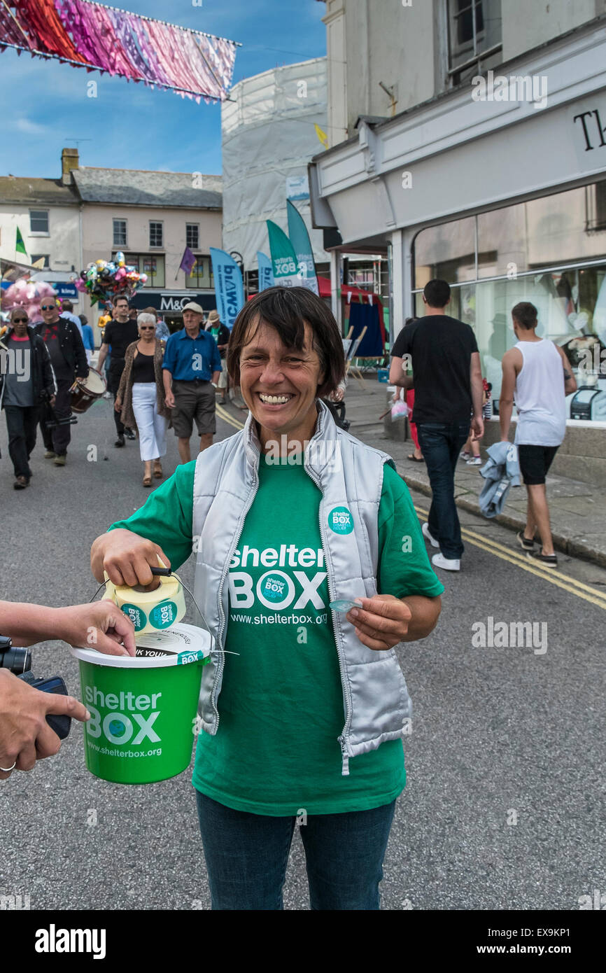 A happy, smiling charity collector collecting donations for the disaster relief charity Shelter Box in Cornwall, - Stock Image