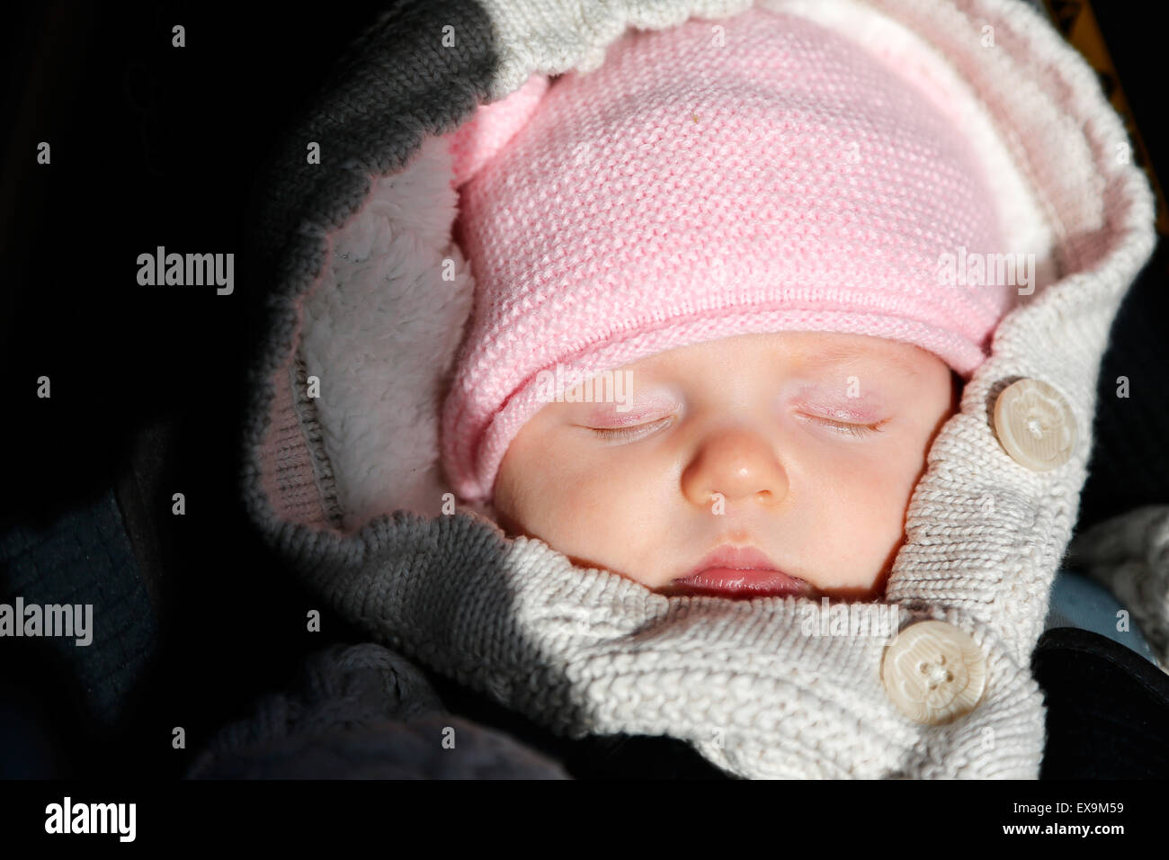 A baby wrapped in warm winter clothing, cosy and warm asleep in her pushchair despite the cold english winter - Stock Image