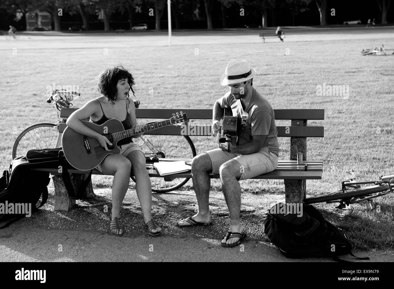 Couple duet singing & playing guitar guitars on public park bench in Annecy France - Stock Image