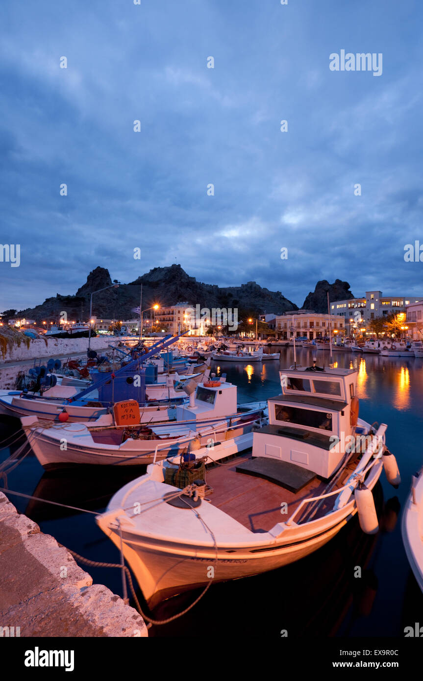 Myrina's quay with caslte, buildings and wooden fishing boats anchored in the quay at twilight. Lemnos or Limnos - Stock Image
