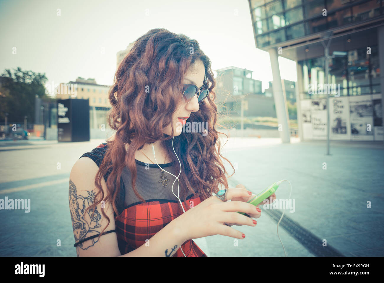young beautiful hipster woman with red curly hair listening music in the city - Stock Image