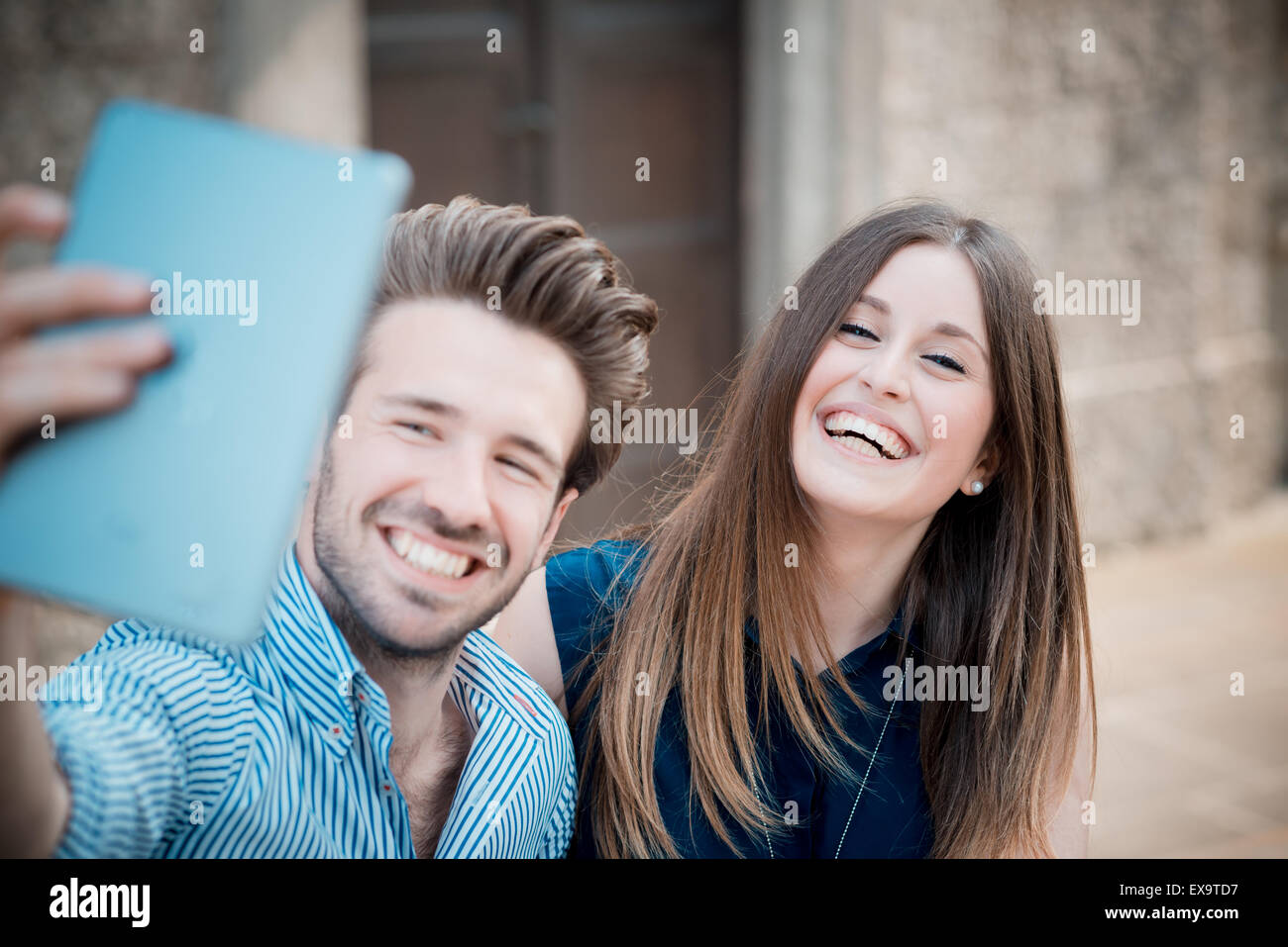 young beautiful couple lovers using tablet outdoors - Stock Image