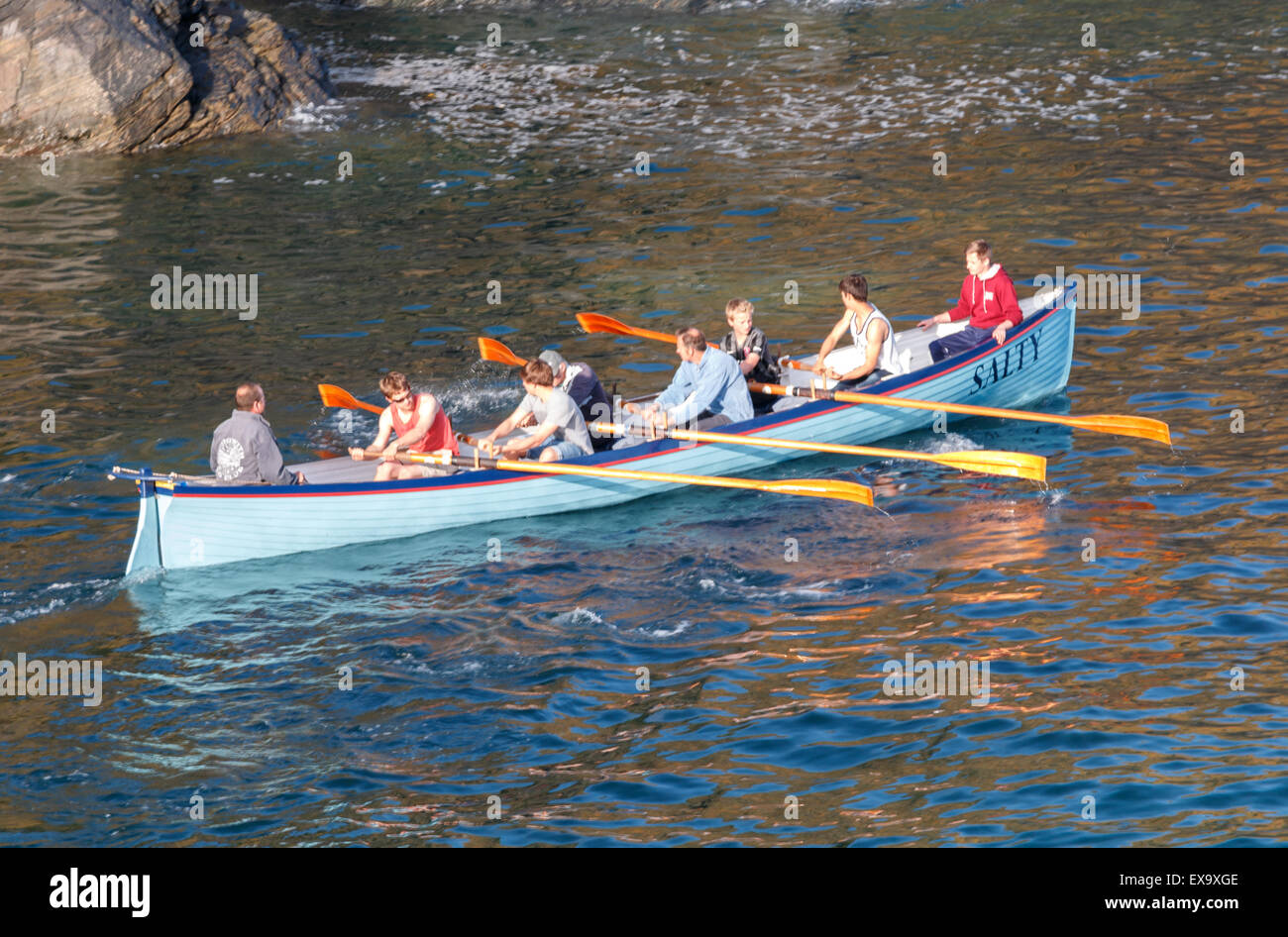 Gig racing - the rowers get the boat moving across the sea  at  Cadgwith Cove Cornwall - Stock Image