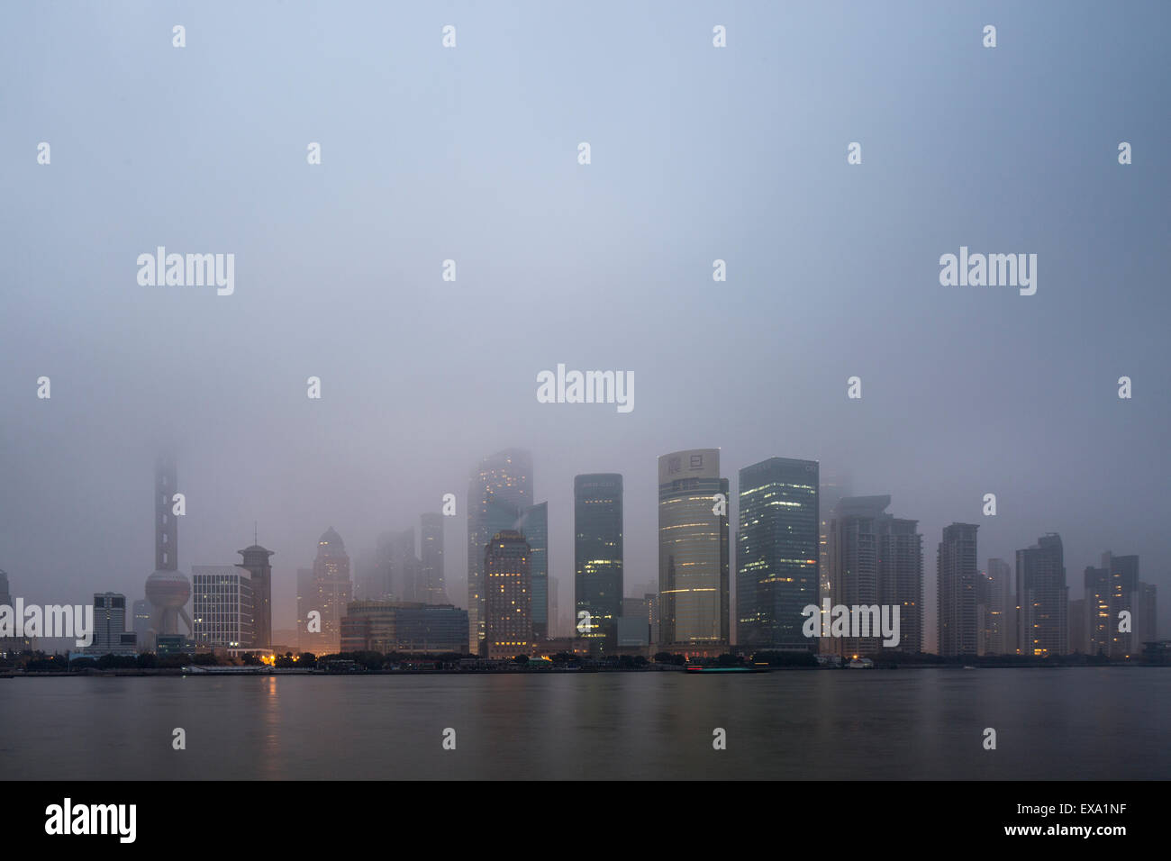 China, Shanghai, Skyscrapers in skyline of Pudong District lost in low clouds along Huangpu River on winter morning Stock Photo