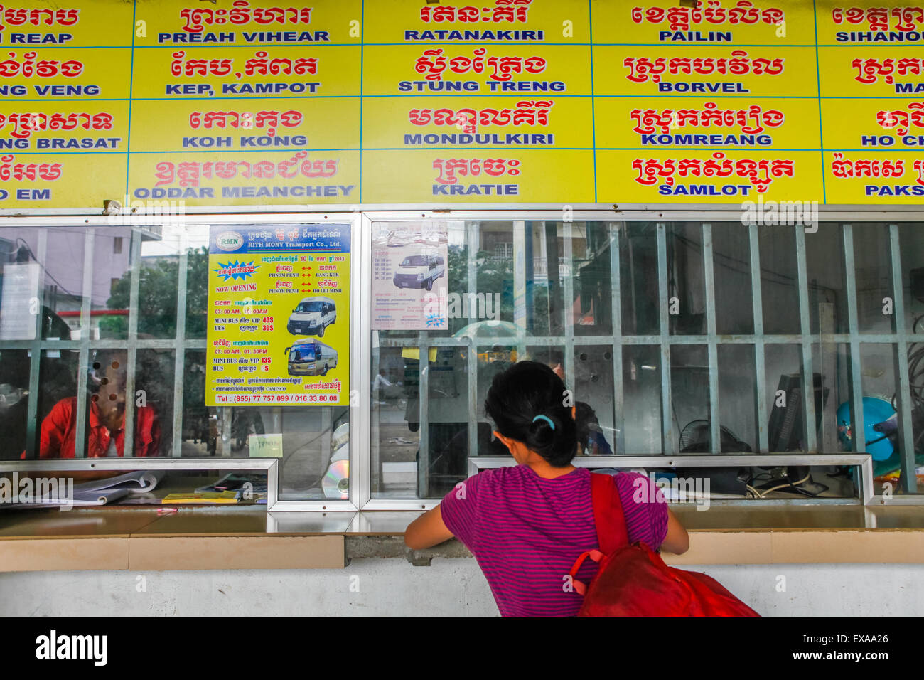 A woman buying intercity bus tickets at the Phnom Penh bus station, Cambodia. - Stock Image
