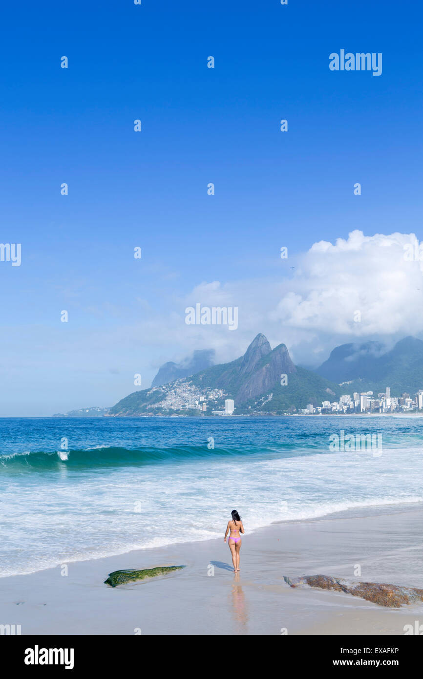 A 20-25 year old young Brazilian woman on Ipanema Beach with the Morro Dois Irmaos hills in the distance, Rio de - Stock Image