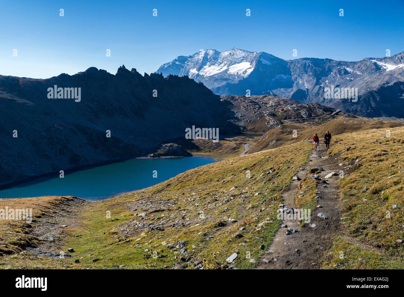 Hikers walking on the Colle del Nivolet beside Rossett Lake, Gran Paradiso National Park, Alpi Graie (Graian Alps), - Stock Image