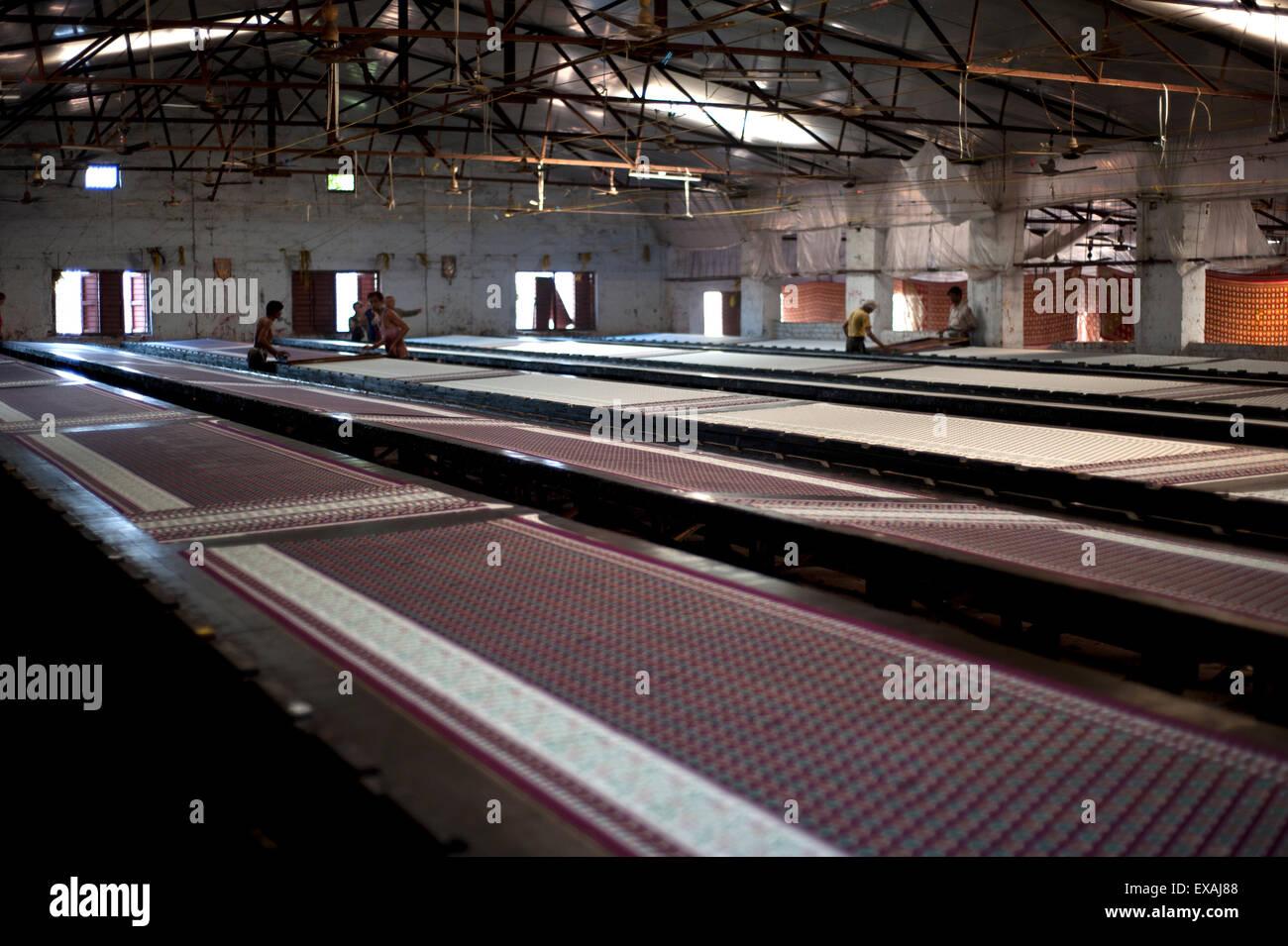 Screenprinting factory, men printing sari lengths of cotton by hand, Bhuj district, Gujarat, India, Asia - Stock Image