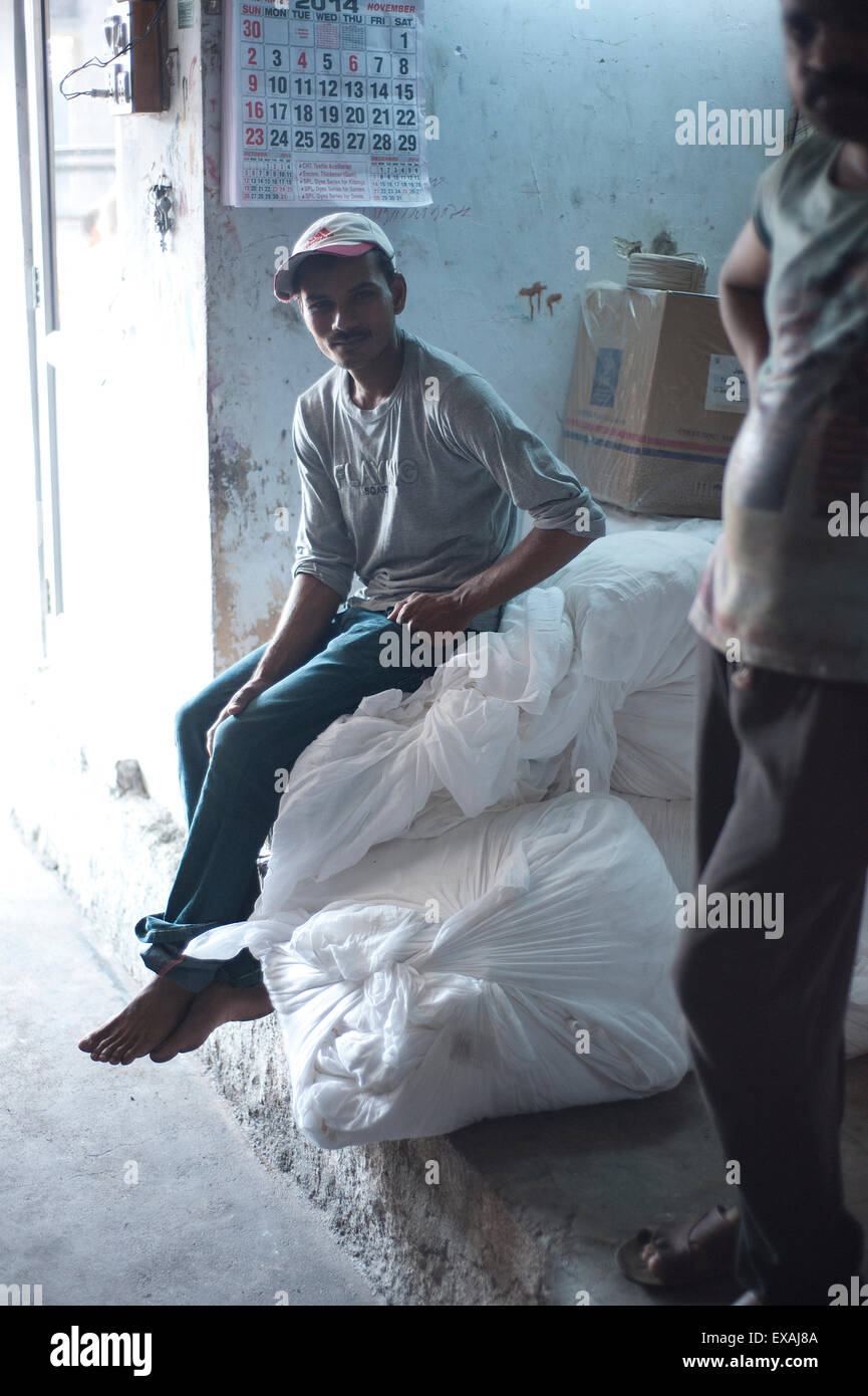 Silkscreen worker pausing from work, sitting on bags of cotton fabric, Bhuj district, Gujarat, India, Asia - Stock Image
