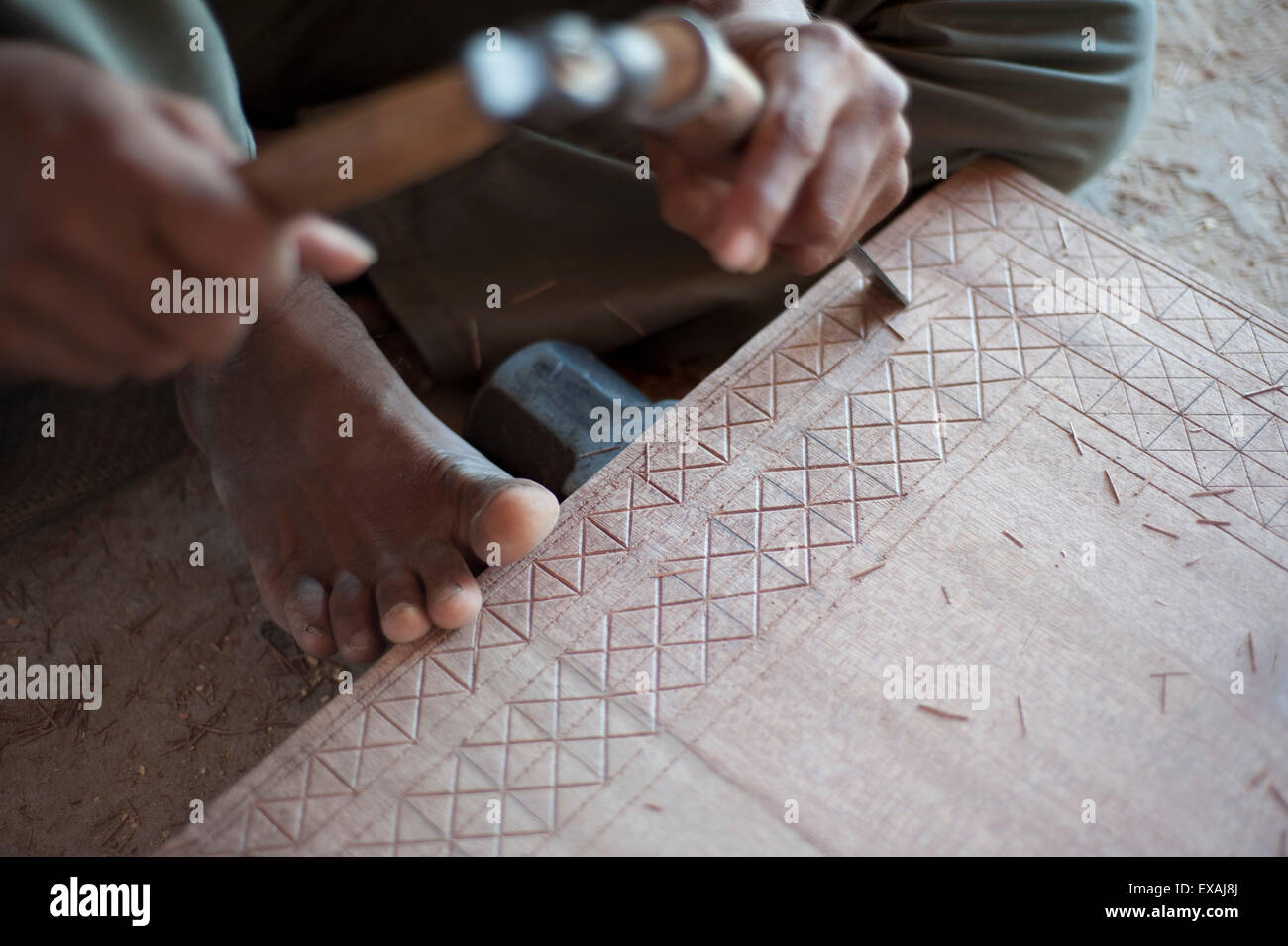 Carpenter chiselling traditional pattern in a piece of wood ready for varnishing, Soyla, Kachchh (Kutch), Gujarat, - Stock Image