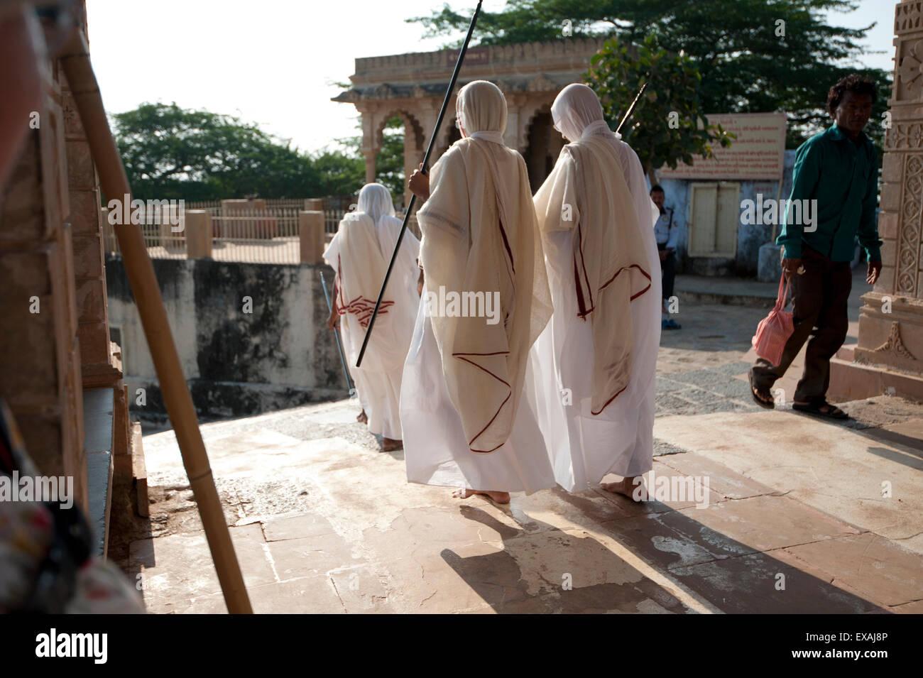Jain pilgrims in white robes, returning down Shatrunjaya Hill after walking up to Jain shrines at dawn, Palitana, - Stock Image