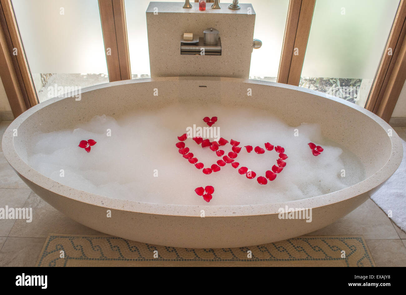Romantic bath tub that is filled with bubbles and rose in the shape ...