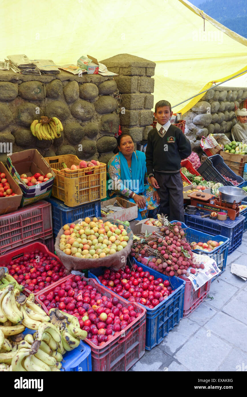 Fresh fruit seller with her son smartly dressed in his school uniform in the centre of Manali, Himachal Pradesh, - Stock Image