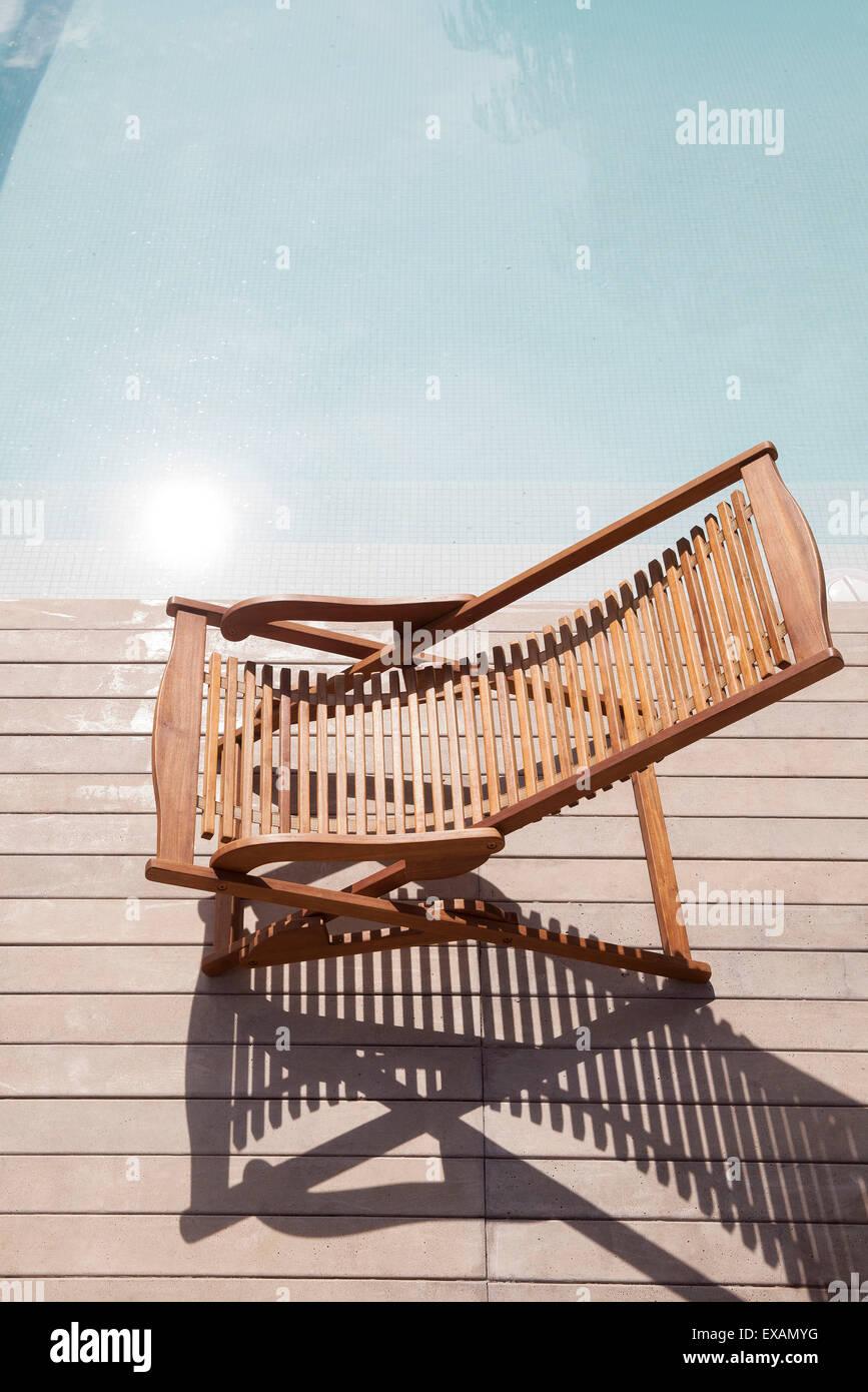Wooden deckchair beside pool - Stock Image