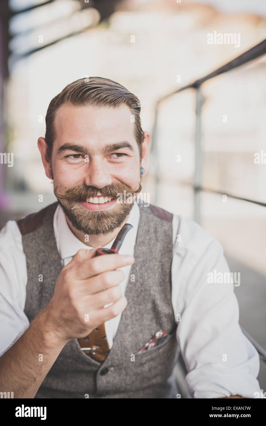 handsome big moustache hipster man smoking pipe in the city - Stock Image