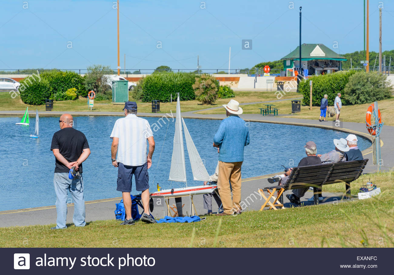 Group of men at a small lake with radio controlled yachts. - Stock Image