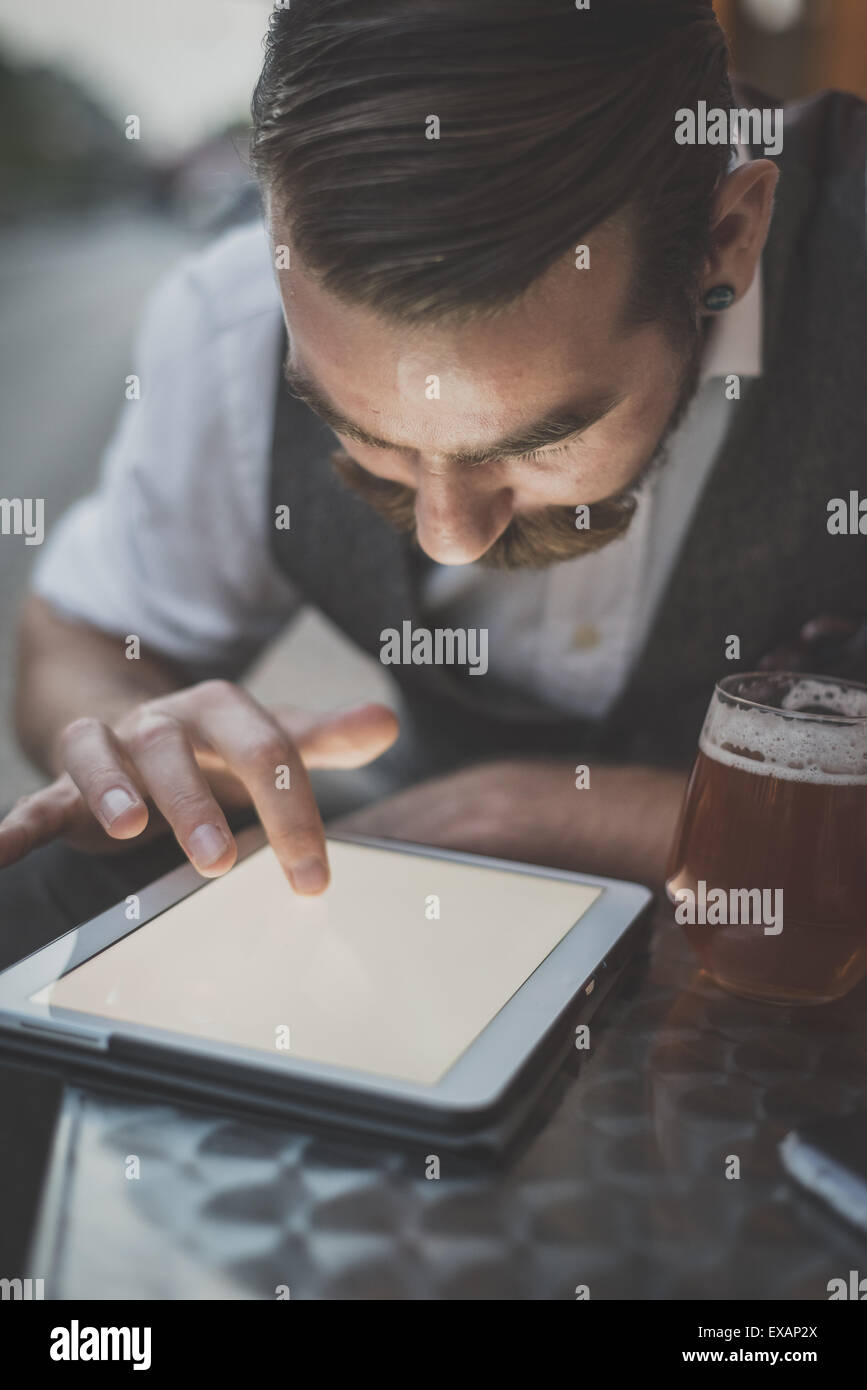 handsome big moustache hipster man using tablet sitting at the bar - Stock Image