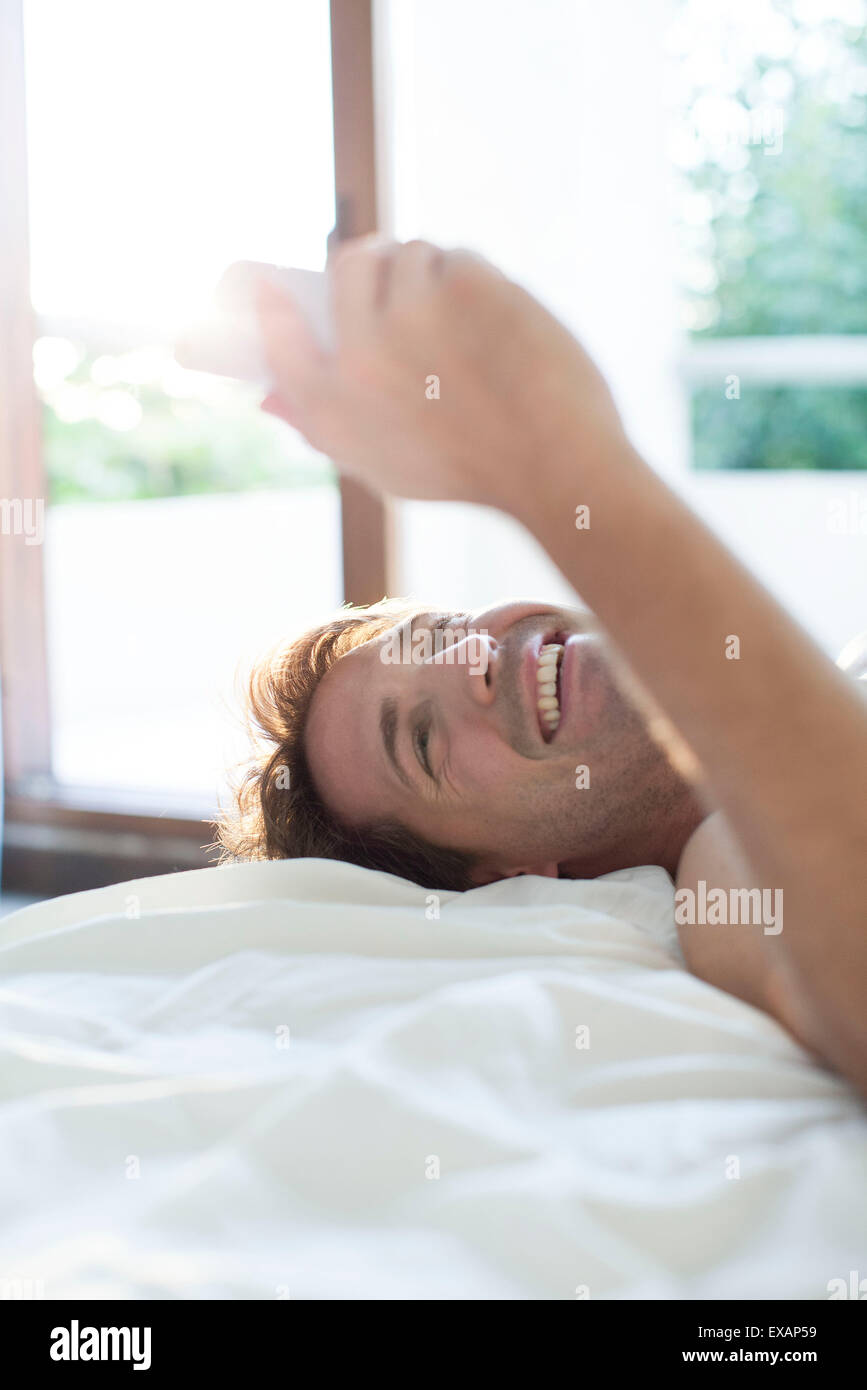 Man lying in bed using multimedia smartphone for instant messaging - Stock Image