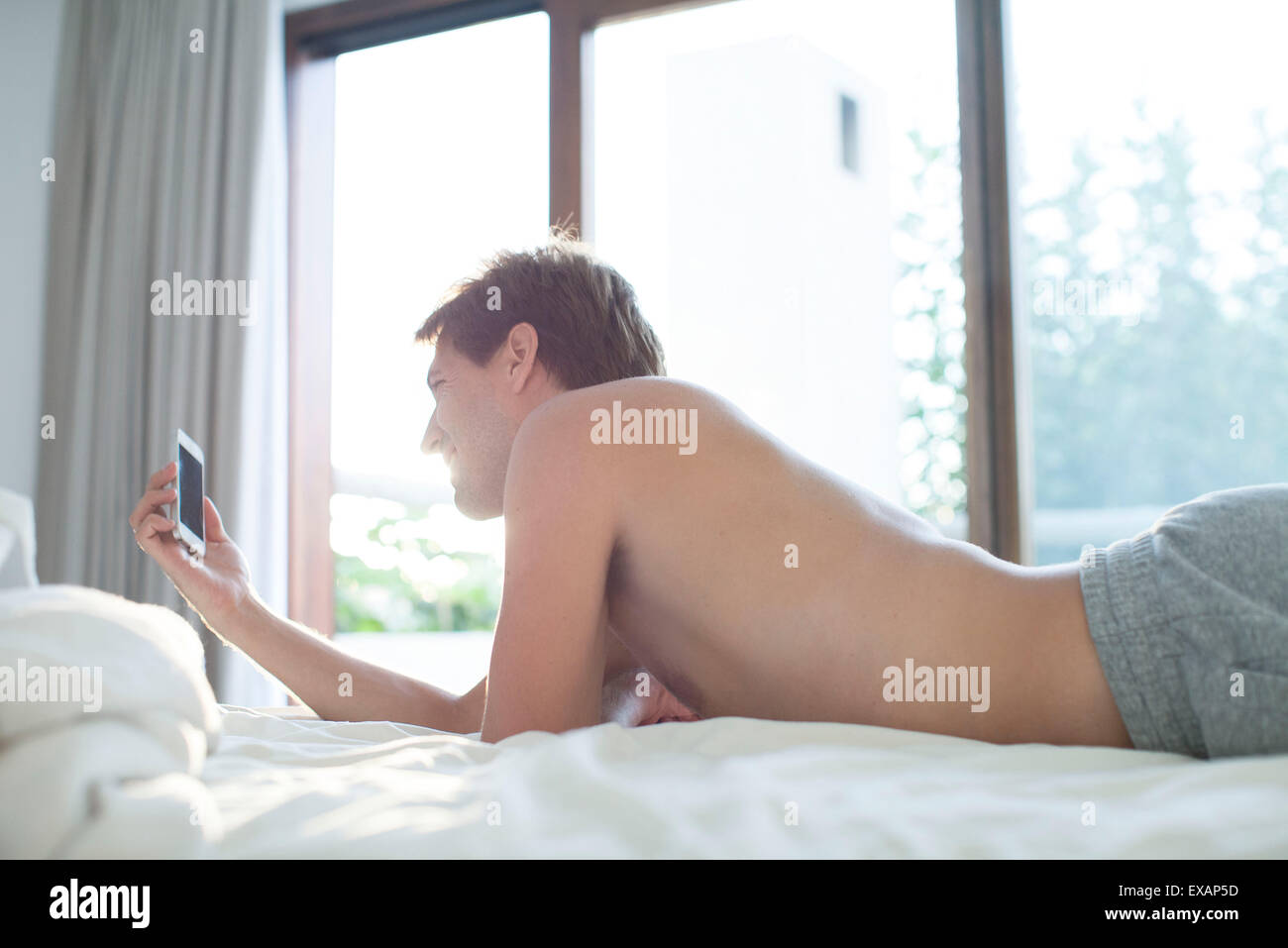 Man lying in bed using multimedia smartphone - Stock Image