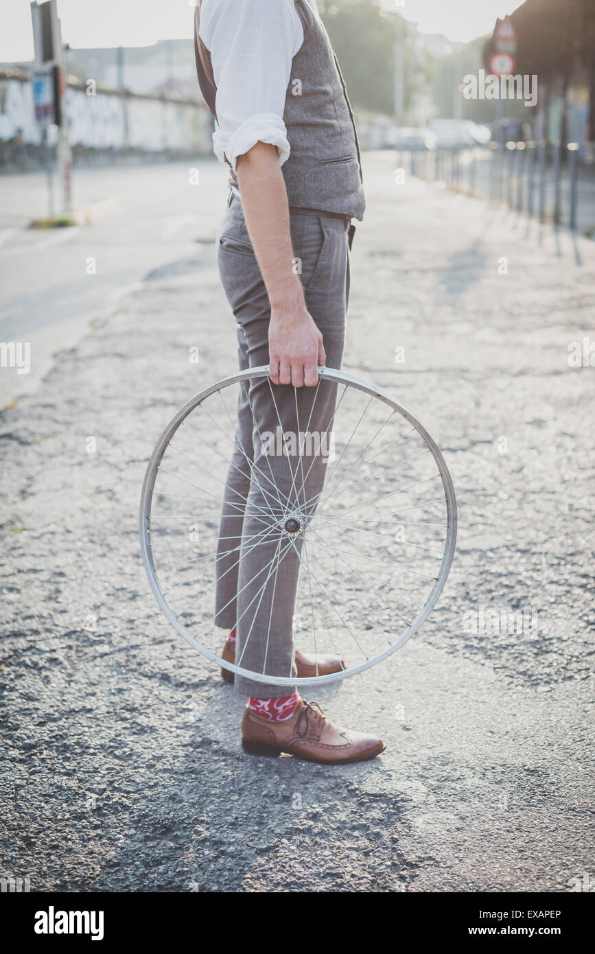 close up of legs shoes hipster man holding old bicycle wheel in the city - Stock Image