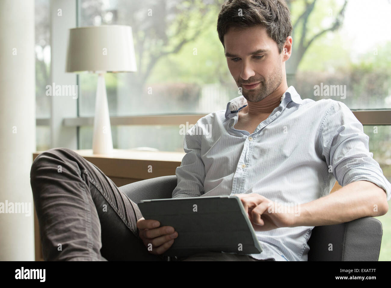 Man using digital tablet at home - Stock Image