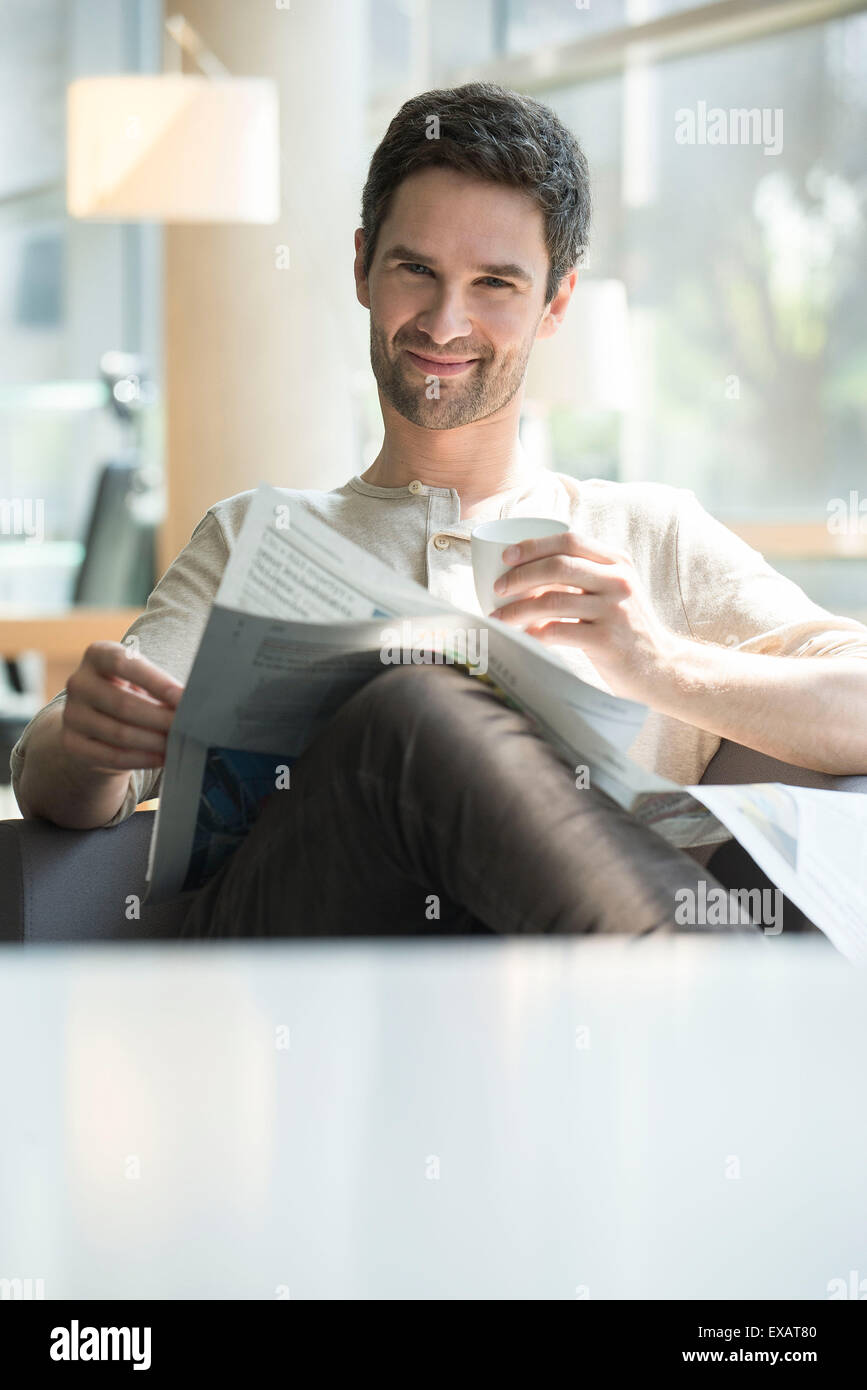 Man relaxing with coffee and newspaper - Stock Image