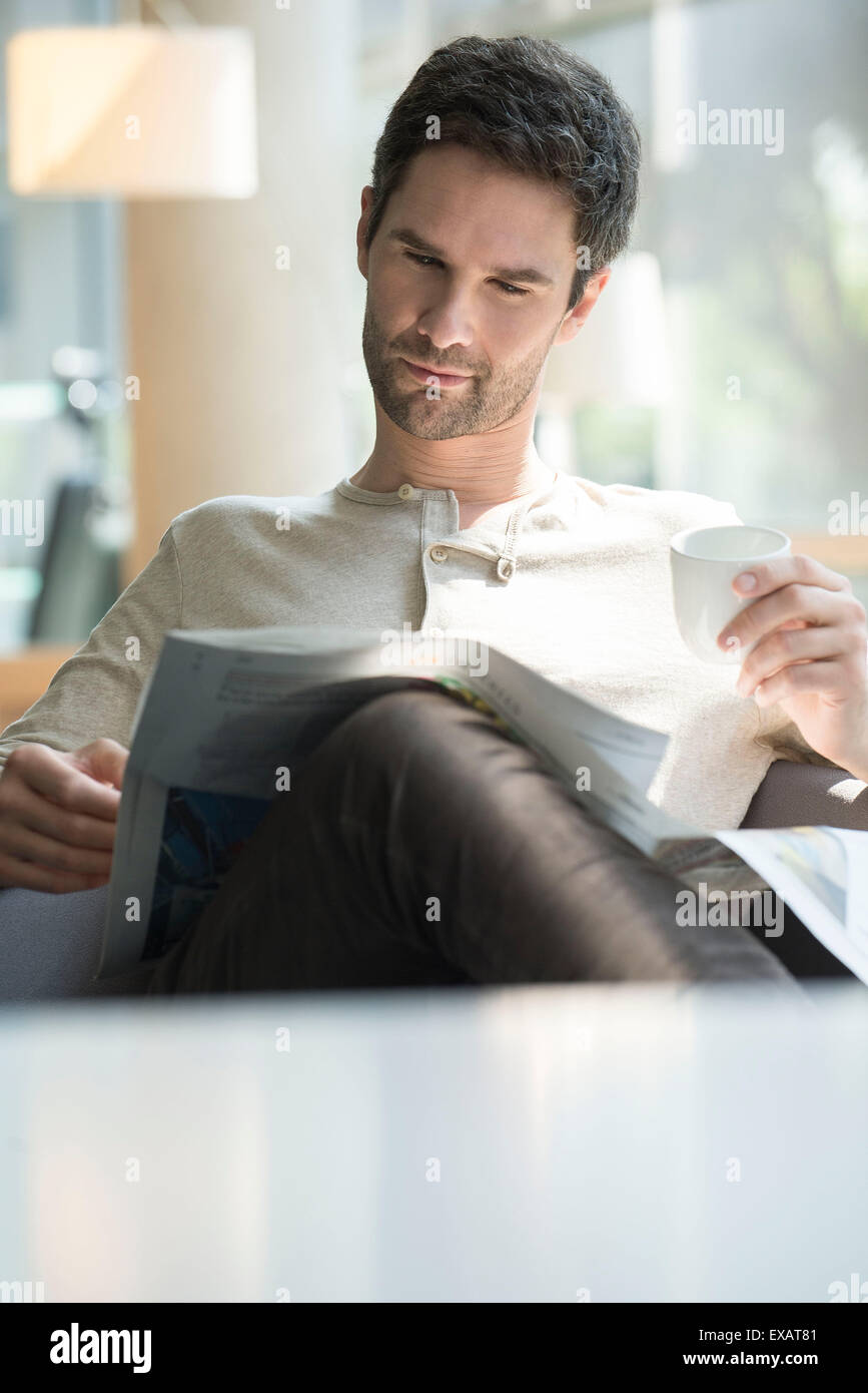 Man reading newspaper and drinking coffee - Stock Image