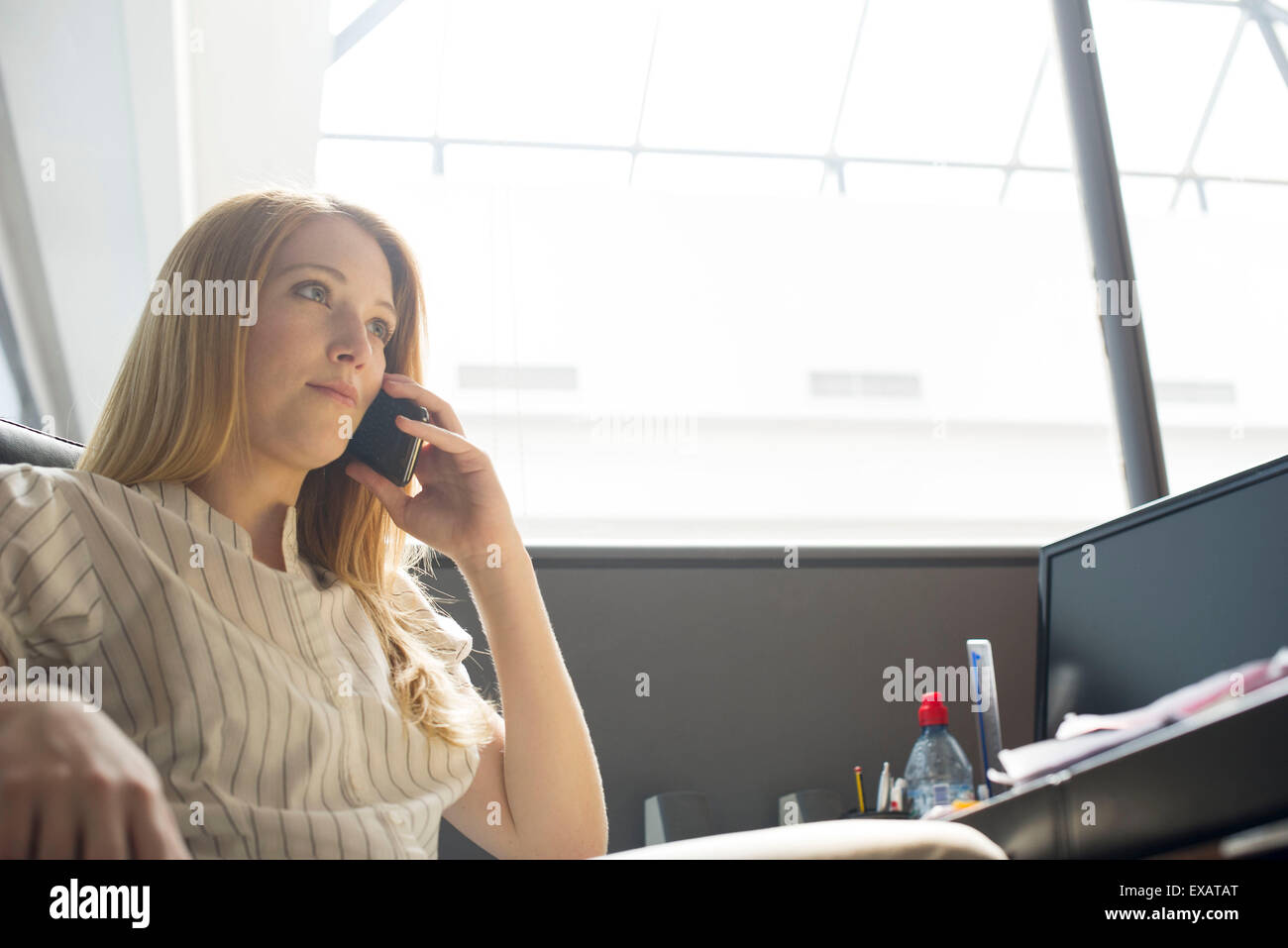 Office worker making phone call at desk - Stock Image