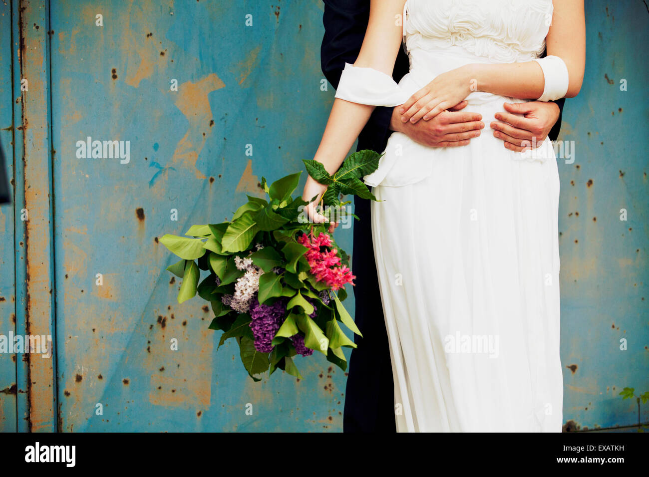 groom hugs his bride, medium close-up - Stock Image