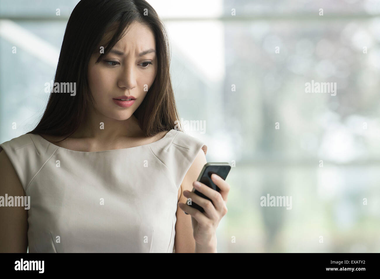 Woman receiving bad news on smartphone - Stock Image