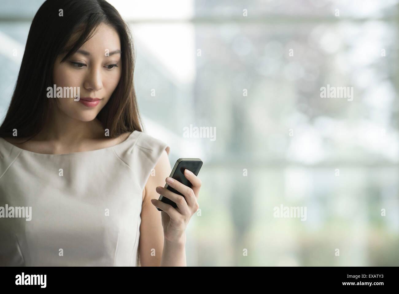 Businesswoman using smartphone - Stock Image