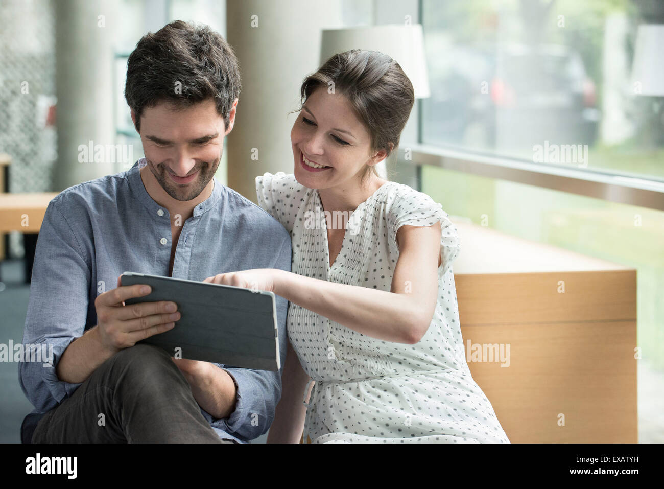 Couple using digital tablet together at home - Stock Image