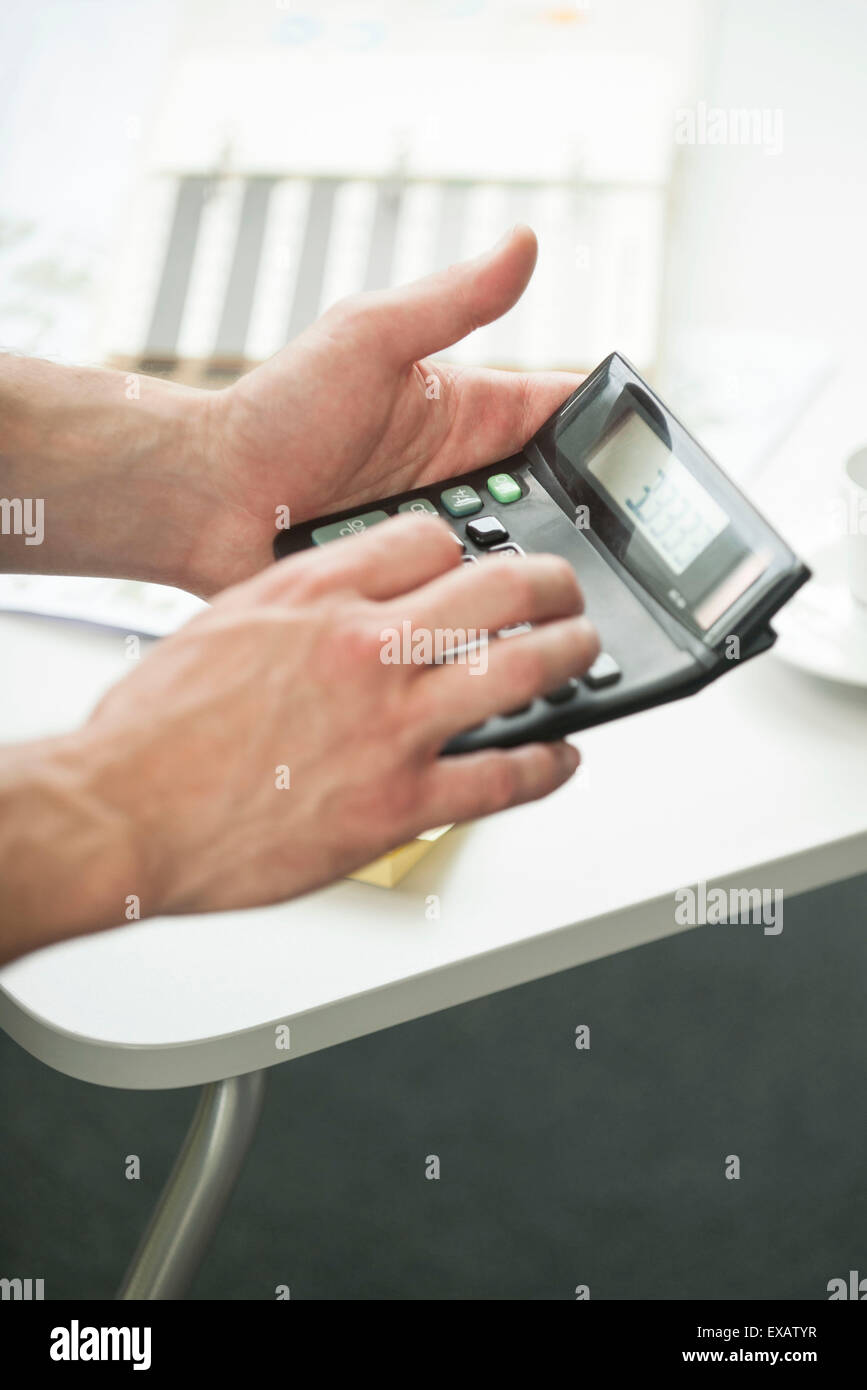 Man's hands holding calculator - Stock Image