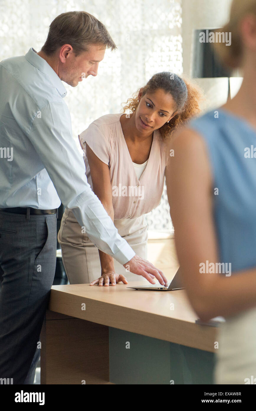 Salesman demonstrating laptop computer for customer - Stock Image