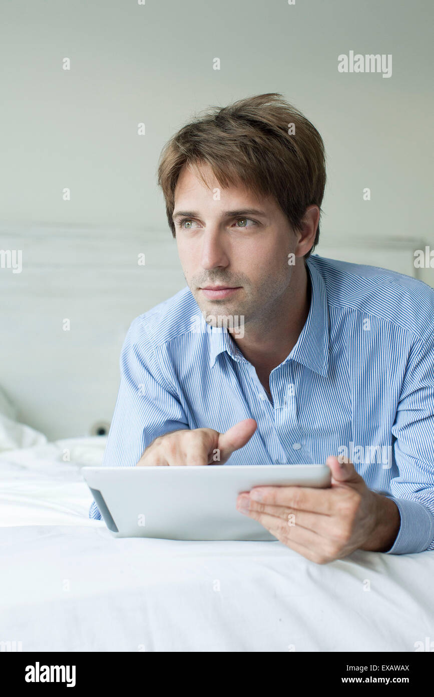 Man lying in bed using digital tablet, looking away with contemplative look - Stock Image