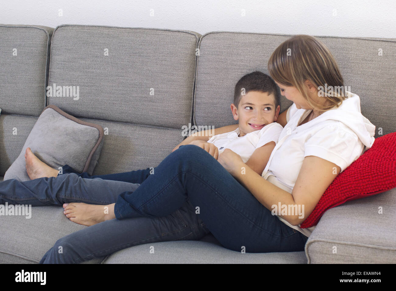Mother and son relaxing together on sofa - Stock Image