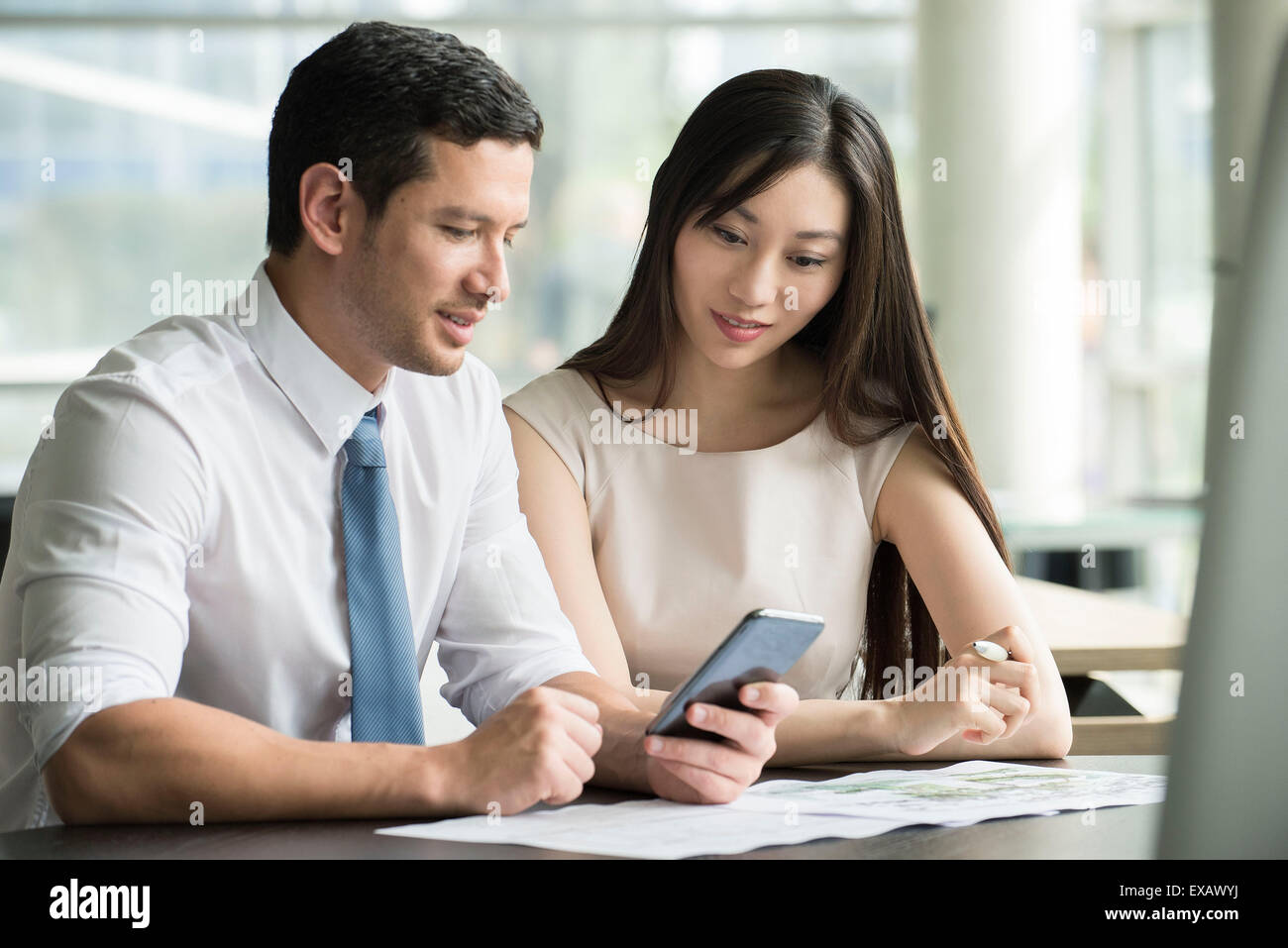 Colleagues looking at smartphone together in office Stock Photo