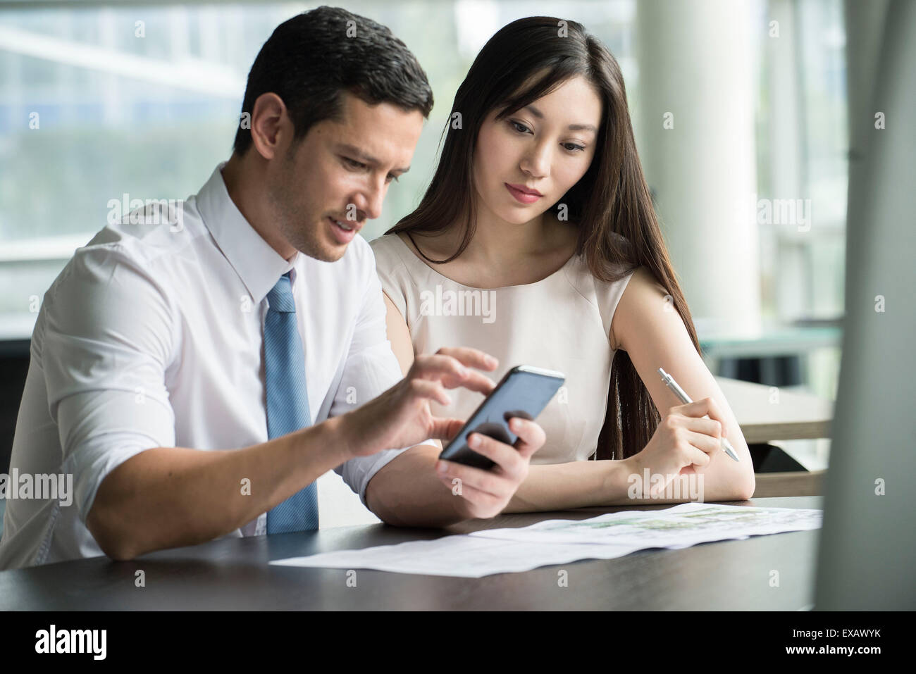 Officer worker showing colleague smartphone Stock Photo