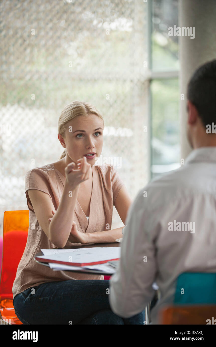 Woman having informal meeting with colleague in cafe - Stock Image
