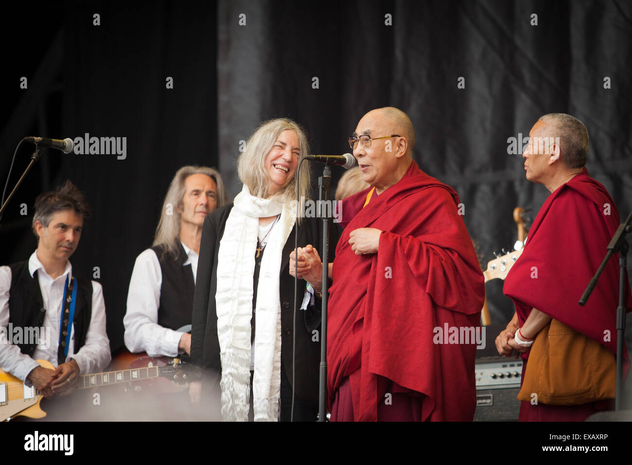 His Holiness the Dalai Lama on the Pyramid Stage with Patti Smith and her band at Glastonbury 28th June 2015ith - Stock Image