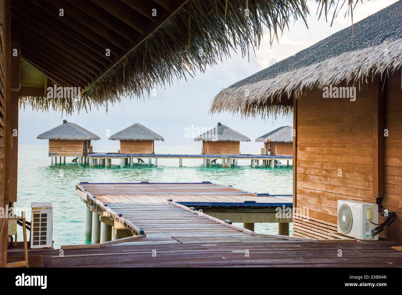 Water huts of an island resort in a shallow lagoon in Maldives - Stock Image
