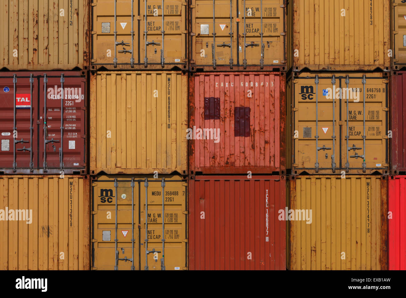 Various brands and colors of shipping containers stacked - Stock Image