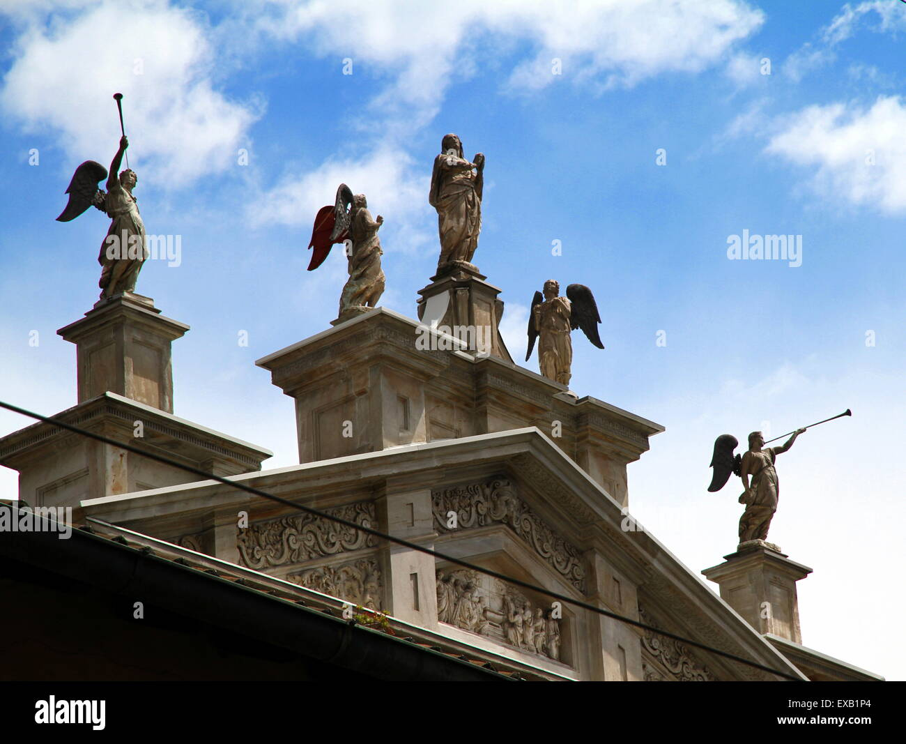 Saints and divine statues on the top of a church in Milan, Italy - Stock Image