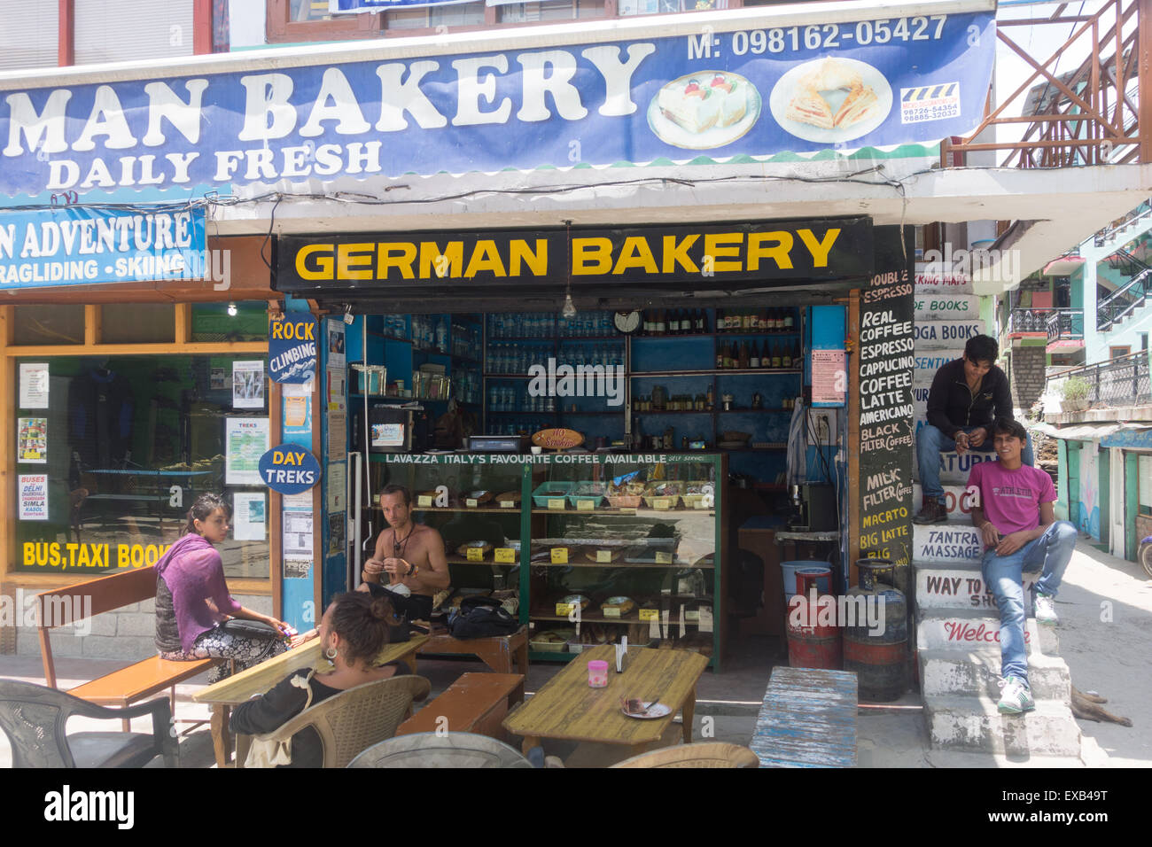 Tourists and locals sitting outside a German Bakery in the popular Himalayan tourist town of Manali,  Himachal Pradesh, - Stock Image
