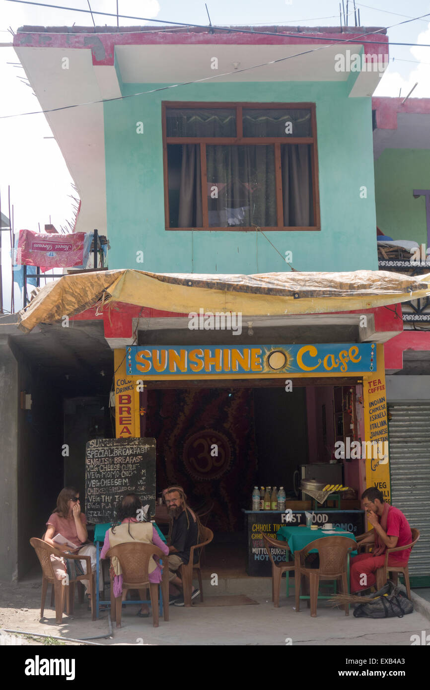 tourists sitting in the shade outside Sunshine Cafe in Manali, in the Indian state of Himachal Pradesh - Stock Image
