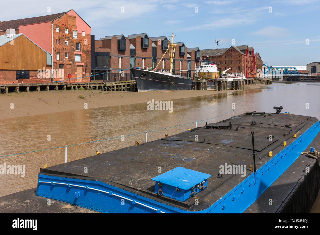 River Hull at low tide with an obsolete ship aground in the mud bank flanked by office and other buildings. - Stock Image