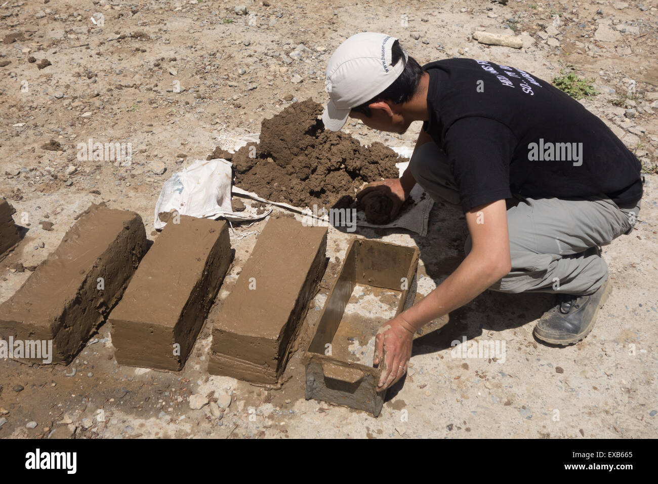 A worker making sustainable mud bricks to construct a greenhouse to grow food all year round - Himalayas - Stock Image
